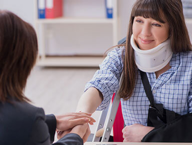 Woman in neck brace shaking hands with lawyer