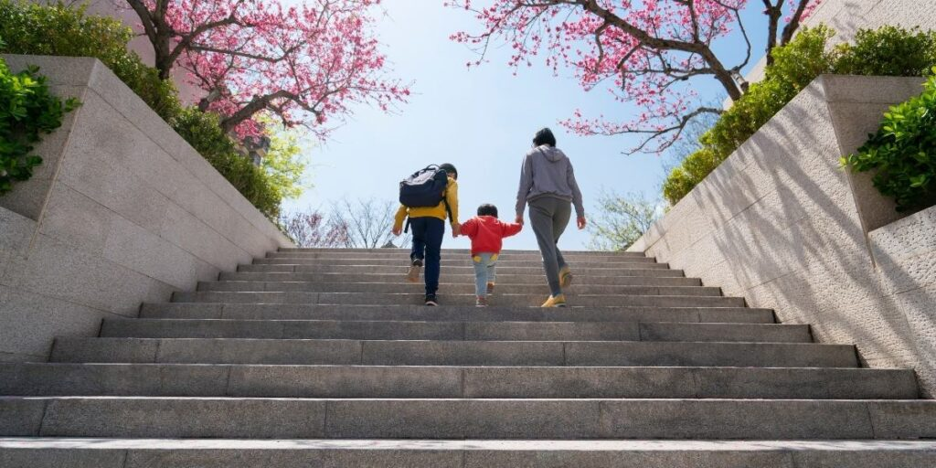 2 adult and a kid climbing steps